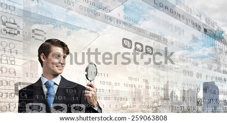 Young businessman with glass magnifier on digital background - stock photo