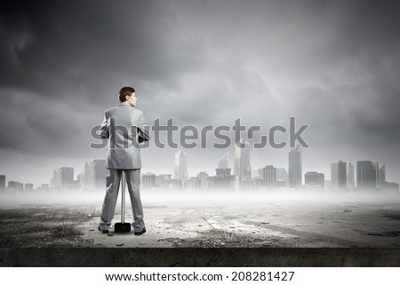 Young businessman with hammer and city at background
