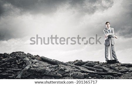 Young businessman with hammer standing on ruins