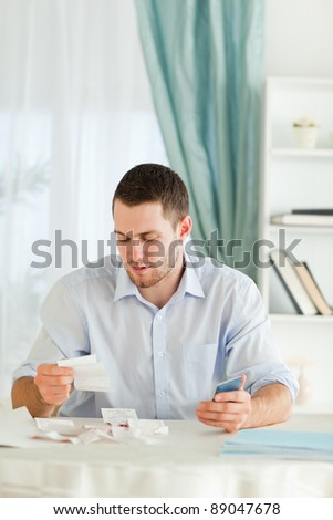 Young businessman with hand calculator checking bills