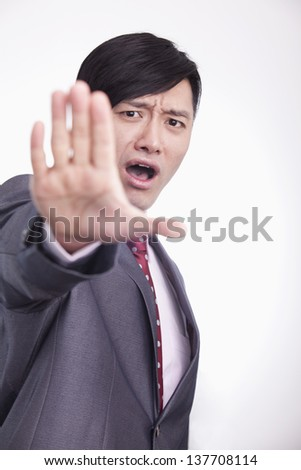 Young businessman with hand raised in stop gesture, studio shot - stock photo