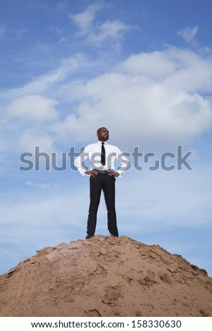 Young businessman with hands on hips in the desert - stock photo