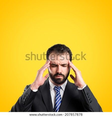 Young businessman with headache over yellow background  - stock photo