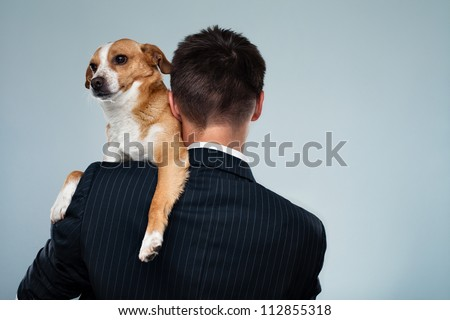 Young businessman with his dog on his shoulder - stock photo