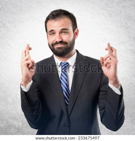 Young businessman with his fingers crossing over textured background