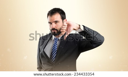 Young businessman with his thumb down over ocher background.  - stock photo