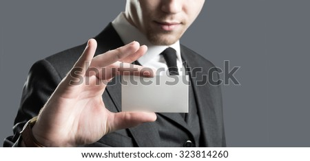 Young businessman with holding up his blank white card card to show his credentials and qualification.  - stock photo