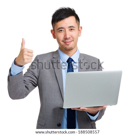 Young businessman with laptop and thumb up
