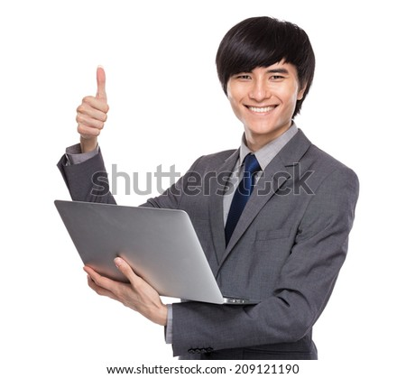 Young businessman with laptop computer and thumb up - stock photo