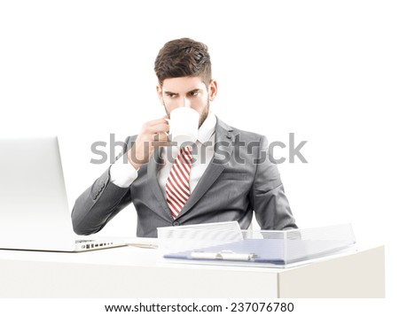 Young businessman with laptop sitting at office while drinking tea against white background. Business people. - stock photo