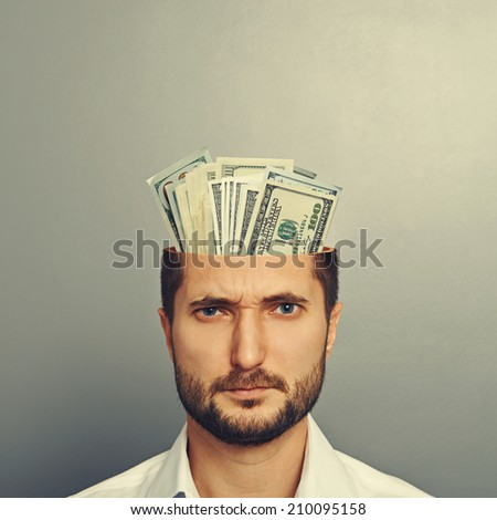 young businessman with money in the head over grey background - stock photo