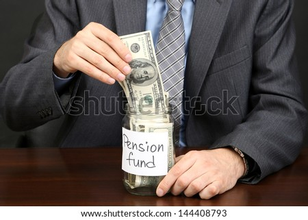 Young businessman with money on black background