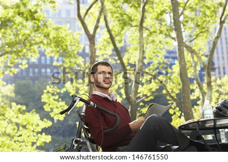 Young businessman with newspaper looking away in park - stock photo