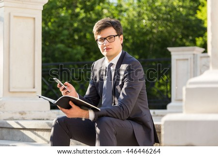 Young businessman with notepad and mobile phone in hand sitting outside with concrete columns and trees in the background