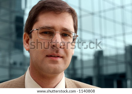 Young businessman with office building in the distance.
