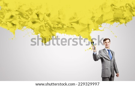 Young businessman with paint brush in hand