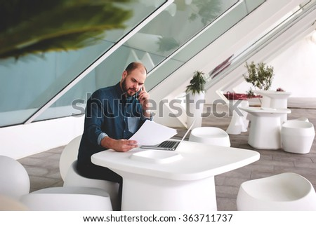 Young businessman with paper documents and open net-book decides important issues via cell telephone while sitting in office interior, male entrepreneur talking on mobile phone during reviewing resume