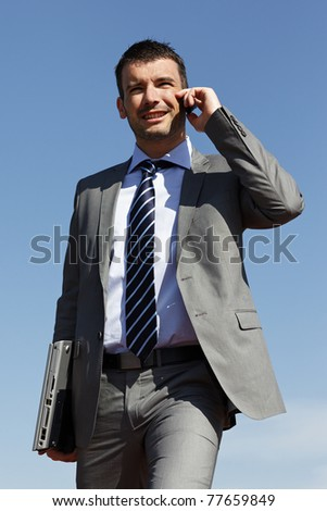 young businessman with phone and blue sky - stock photo