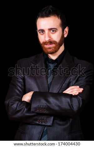 young businessman with red beard on a black background