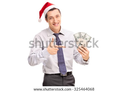 Young businessman with Santa hat holding bunch of money and pointing with his hand towards them isolated on white background - stock photo
