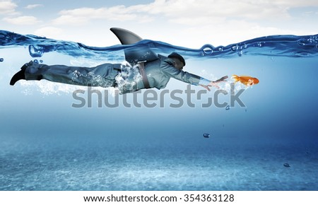 Young businessman with shark flipper swiming under water - stock photo
