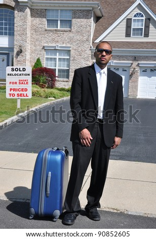 Young Businessman with suitcase standing in front of home relocation for sale realtor sign on front yard lawn of brick suburban home - stock photo