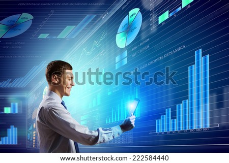 Young businessman with tablet in hands against digital background - stock photo