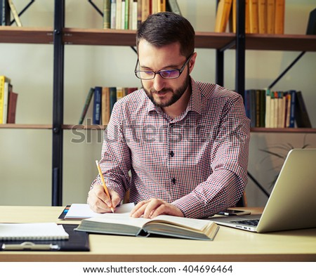 Young businessman with the glasses reading paperwork and taking notes at home office - stock photo