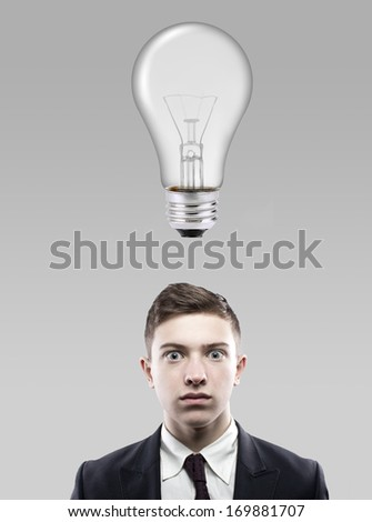 Young businessman with thoughtful expression and light bulb over his head