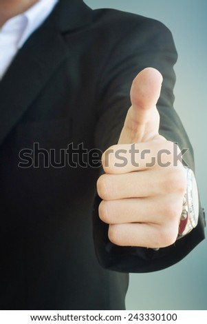 Young businessman with thumb up - stock photo