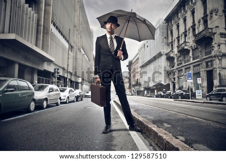 young businessman with umbrella in the city - stock photo