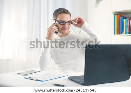 Young businessman working at home using computer and mobile phone