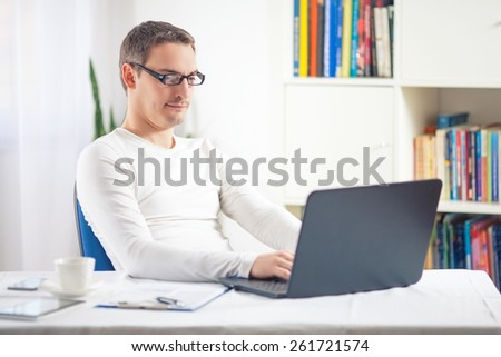 Young businessman working at home using laptop
