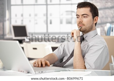 Young businessman working in bright office, sitting at desk, using laptop.? - stock photo