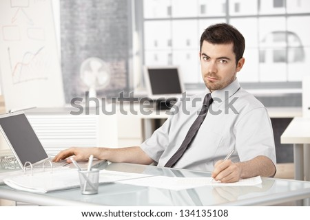 Young businessman working in bright office, using laptop, writing notes.
