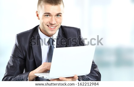 Young businessman working in office, looking at laptop computer screen, smiling. - stock photo