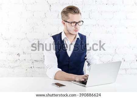 Young businessman working in office, sitting at desk, looking at laptop computer screen, smiling. - stock photo