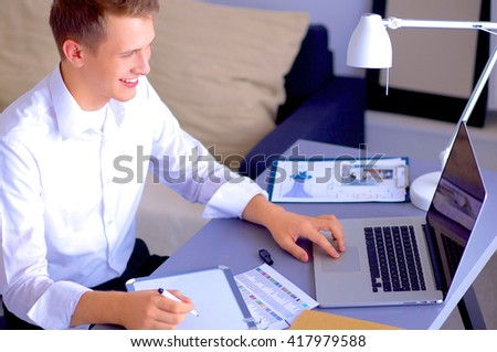 Young businessman working in office, sitting near desk - stock photo