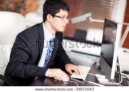 Young businessman working on computer in office. - stock photo