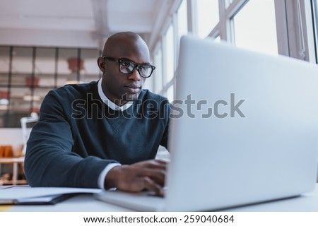Young businessman working on his laptop in office. Young african executive sitting at his desk surfing internet on laptop computer. - stock photo