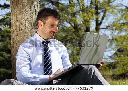 young businessman working on laptop in a park - stock photo
