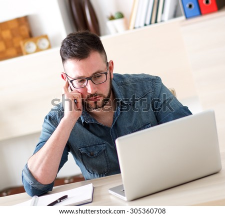Young businessman working on laptop in office - stock photo