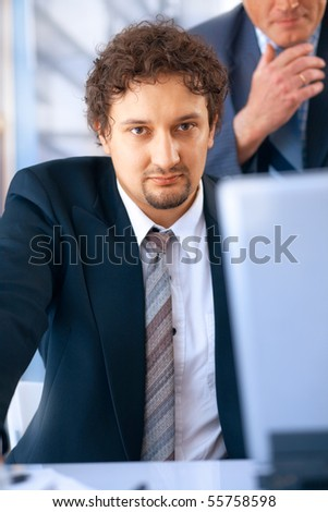 Young businessman working on laptop in the office with his colleague at the back.