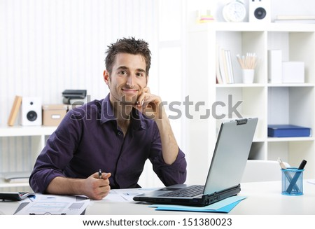 Young businessman working on laptop, looking at camera