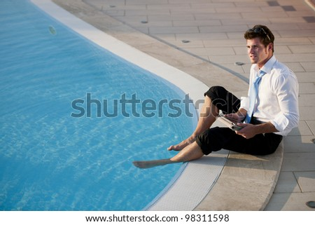 Young businessman working on PC tablet with feet in the pool - stock photo