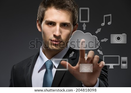 Young businessman working with cloud technology on black background - stock photo