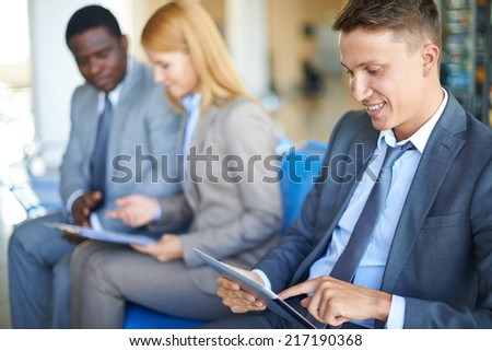 Young businessman working with digital tablet in airport with two colleagues interacting on background