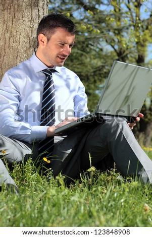 young businessman working with laptop in a park - stock photo