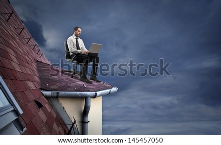 young businessman working with laptop on the roof - stock photo