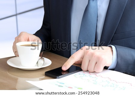 Young businessman working with mobile phone.Graphs  and coffee behind - stock photo